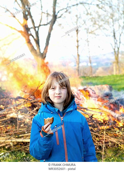Portrait of a Boy in front of Bonfire Holding a Toast
