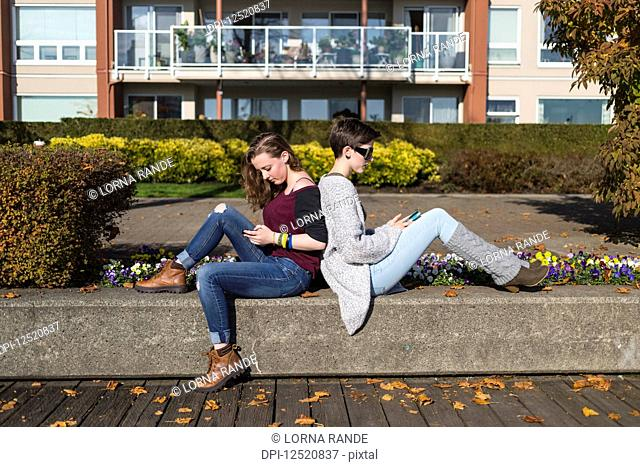 Two young women sit back to back using their smart phones; New Westminster, British Columbia, Canada