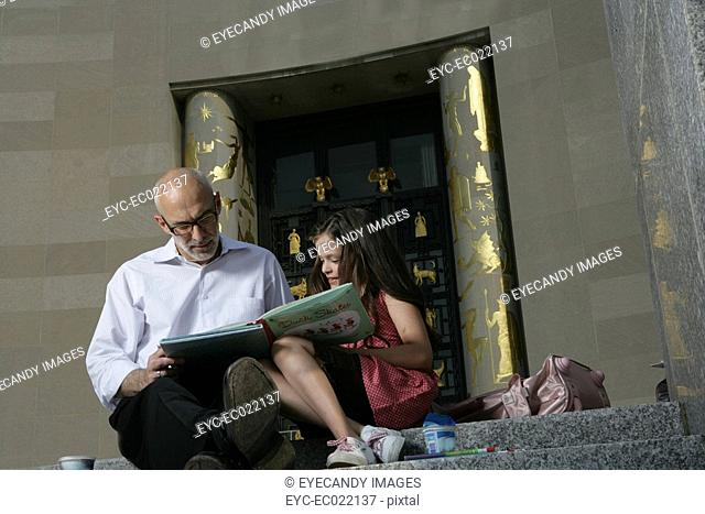 mature man reading with girl