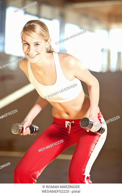 Germany, Mauern, Woman lifting weights, smiling, portrait