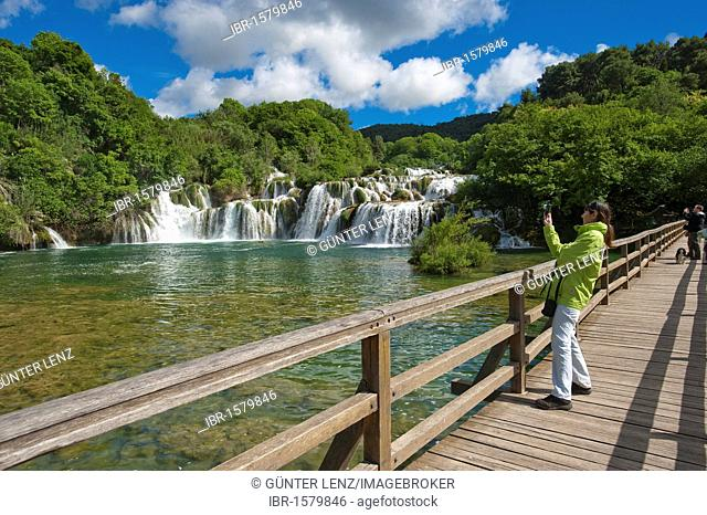 Tourist photographing a waterfall from a wooden bridge, Krka National Park, aeibenik-Knin County, Croatia, Europe