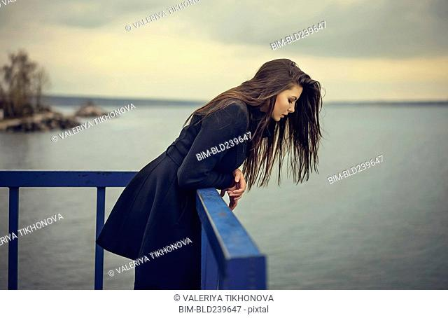 Caucasian woman leaning on railing at waterfront