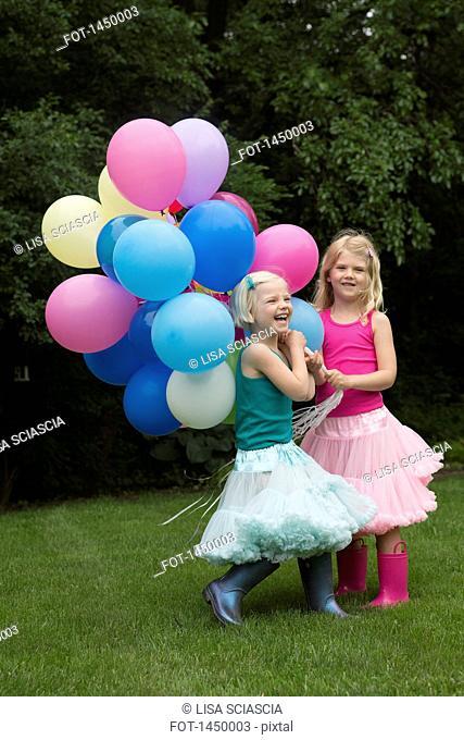 Happy siblings holding balloons in backyard