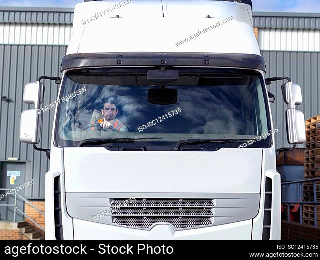 UK, Truck driver in truck cabin in front of warehouse