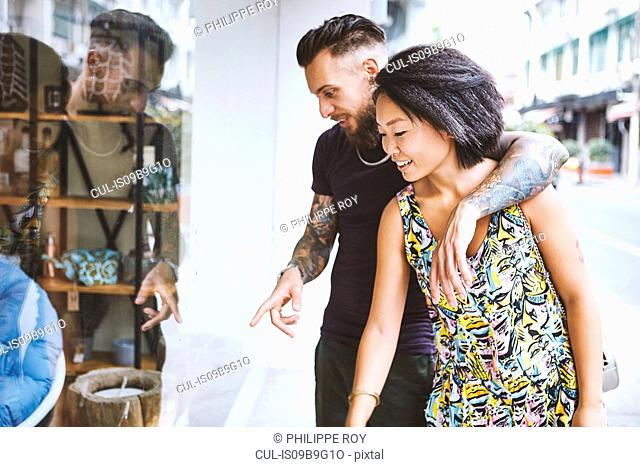 Multi ethnic hipster couple looking and pointing at shop window, Shanghai French Concession, Shanghai, China