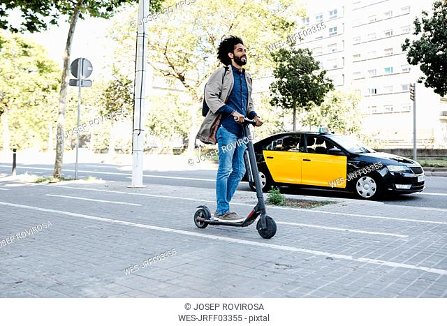 Man with backpack riding his E-Scooter on a bicycle lane