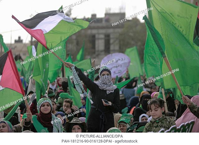 16 December 2018, Palestinian Territories, Gaza City: Palestinian women wave flags during a rally marking the 31st anniversary of the founding of the Islamist...