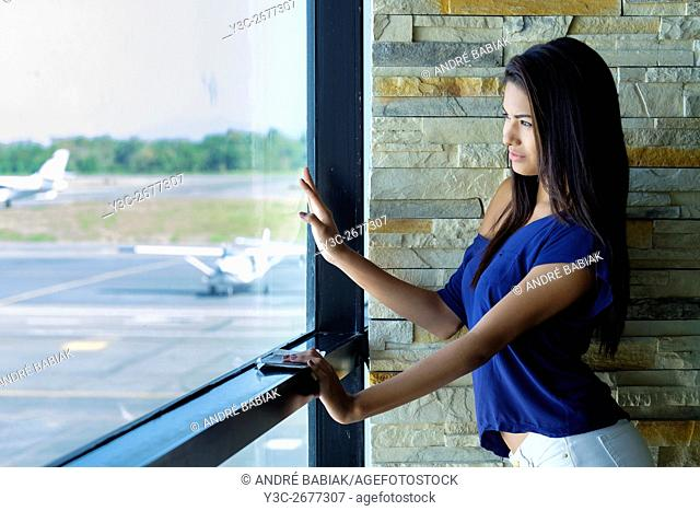 A beautiful young woman watching airplanes at airport terminal