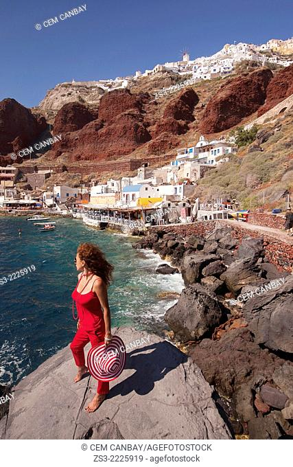 Woman standing on the rocks at the Ammoudi bay, Oia village, Santorini, Cyclades Islands, Greek Islands, Greece, Europe