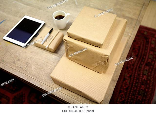 Still life of parcels and digital tablet in picture framers workshop