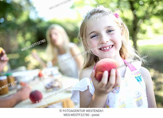 Portrait of smiling girl holding peach outdoors
