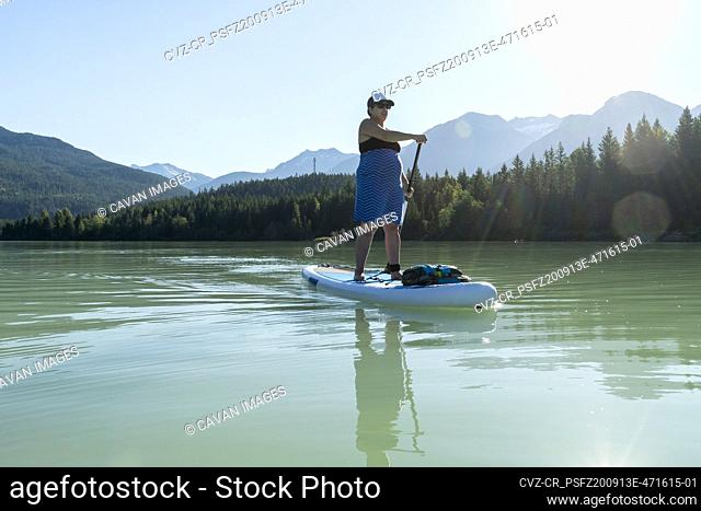 Full body pregnant woman in dress paddleboarding on calm water of lake against mountain ridge and green forest on summer day in British Columbia, Canada