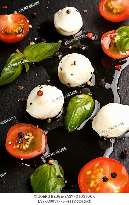 mediterranean salad with cherry tomato, fresh basil, mozzarella and olive oil on slate