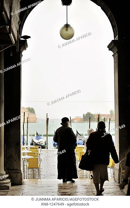 People walked under the arcades of the Piazza San Marco in Venice, Italy