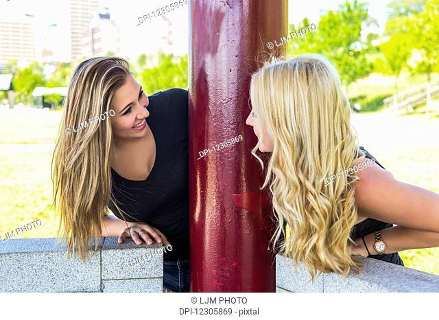 Two girlfriends looking at each other around a pole while enjoying the outdoors in a downtown city park; Edmonton, Alberta, Canada