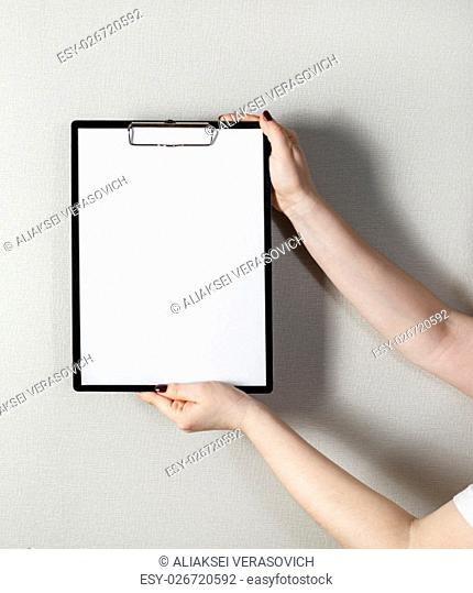 Clipboard with a blank sheet of paper in female hands with a deep shadow on the background of gray wall. Mock-up for design presentations and portfolios