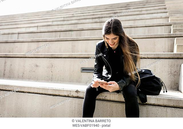Smiling young woman sitting on stairs using cell phone