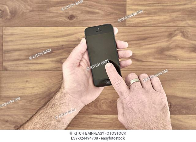 A studio photo of a mobile phone in hand