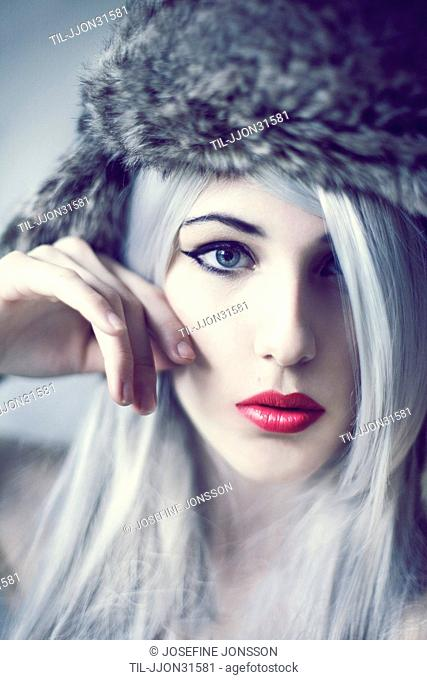 Blonde female youth with red lipstick wearing a fur hat looking dreamy into camera
