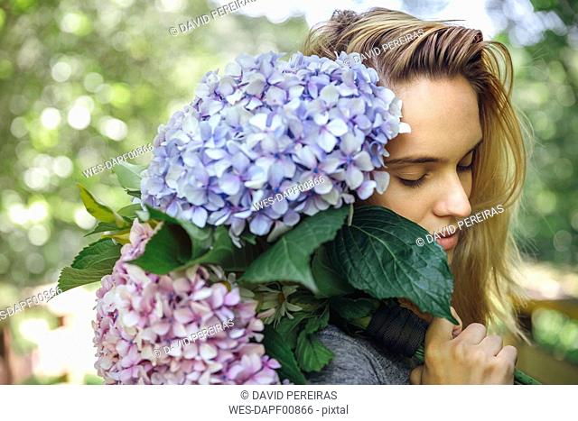 Young woman with closed eyes holding a bouquet of hydrangeas