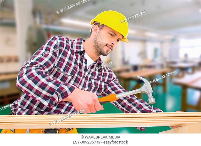 Composite image of handyman using hammer on wood