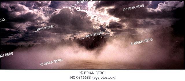 Smoke beneath heavy clouds
