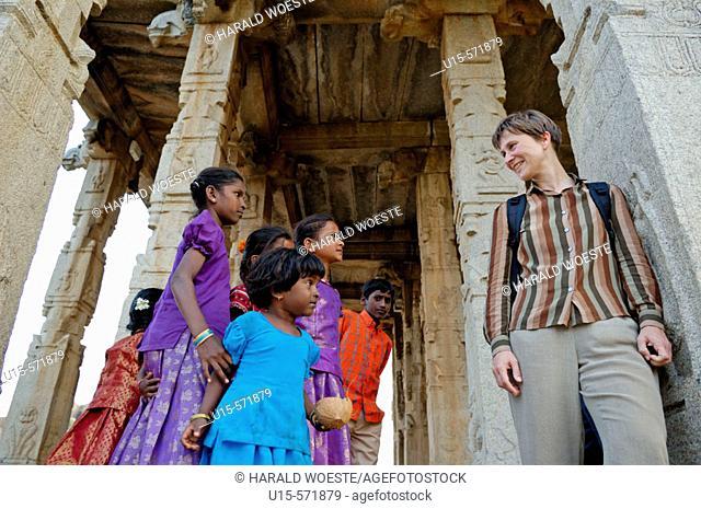A few indian girls talking to a German mid-aged female tourist at Large Ganesha Temple in Hampi, Karnataka, India 2005