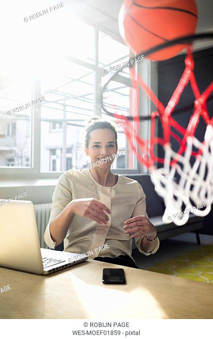 Portrait of smiling freelancer sitting at desk in a loft throwing basketball into hoop