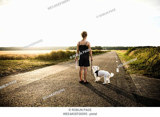 Girl with dog standing on rural road holding miniature wind turbine