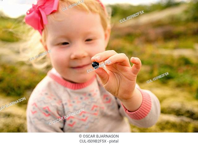 Portrait of young girl outdoors, holding blueberry
