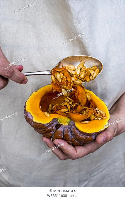Close up of person using silver tablespoon to remove seed from a pumpkin