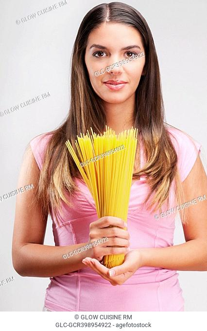 Portrait of a woman holding uncooked spaghetti