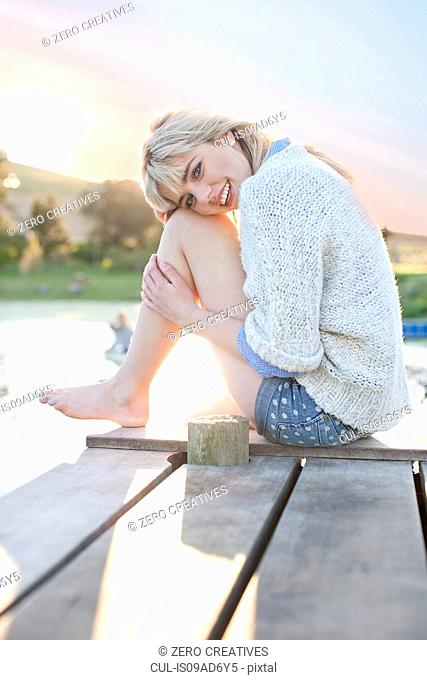 Shy young woman sitting on pier