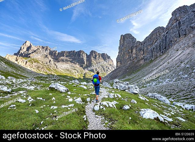 Hiker, mountaineer on a trail between rocky mountains at Forcella Grande, Sorapiss Circuit, behind Mount Punte Tre Sorelle, Dolomites, Belluno, Italy, Europe