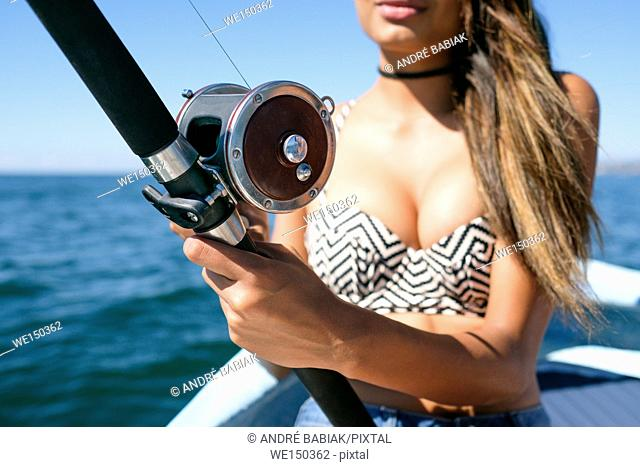 Close up of fishing reel and rod held by attractive young woman on fishing boat