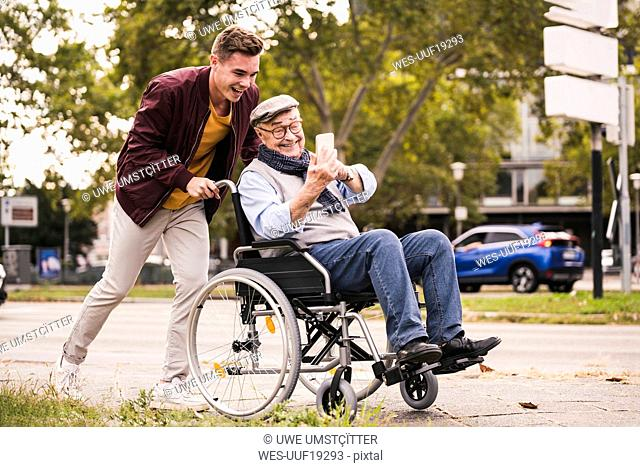 Smiling young man pushing happy senior man with smartphone in wheelchair