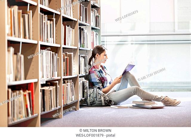 Student reading book at university library