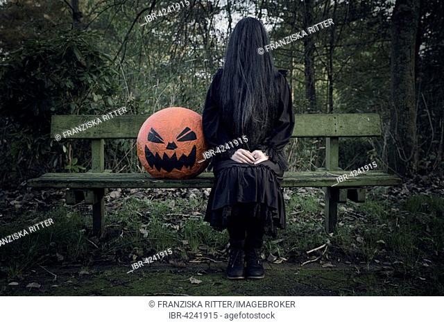 Woman in black, face covered with long black hair, sitting beside a pumpkin, ghost woman with pumpkin head, Halloween
