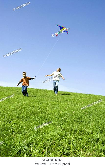 Father and son (4-7) flying kite, low angle view