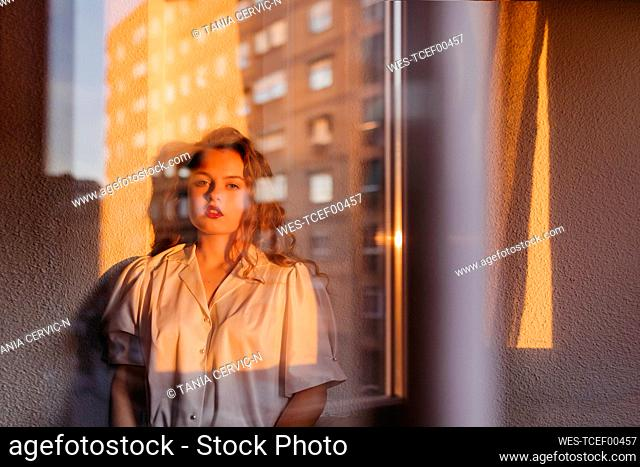 Portrait of beautiful young woman behind windowpane at home