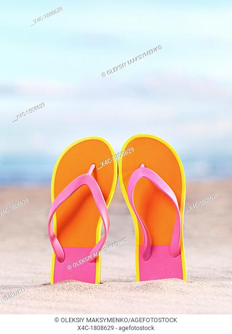 Close up of a pair of bright orange flip flops at the beach under blue sky background