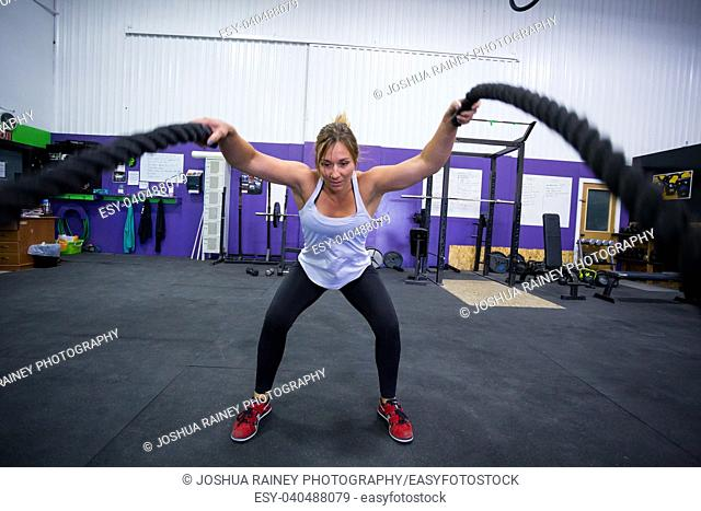 Female working out with ropes doing crosstraining type activities