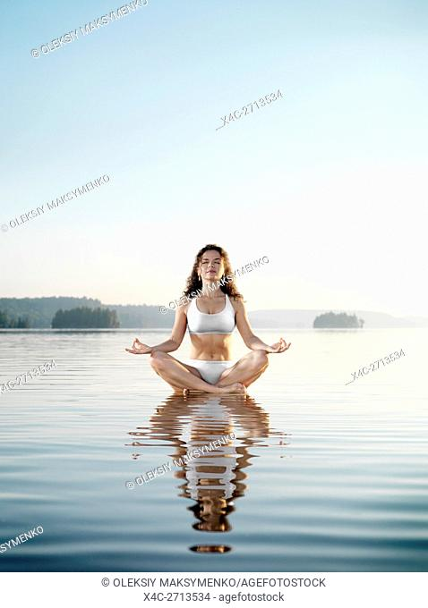 Young woman in white swimsuit meditating. Practicing meditation on a floating platform in calm water on the lake in early morning during sunrise