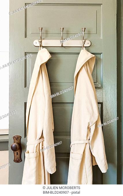 Bathrobes hanging on hooks on door