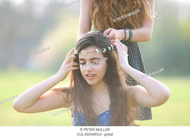 Two teenage girls putting on and wearing daisy chain headdresses in park