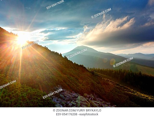 Last sun rays in evening sky with clouds above Syniak mountain. Summer sunset view from Homiak mountain, Gorgany, Carpathian, Ukraine