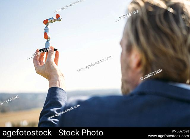 Businessman holding at small robotic arm against clear sky on sunny day