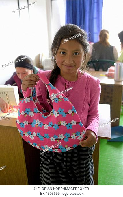 Girl proudly displaying her homemade bag, vocational training, Creciendo Unidos social project, Javier Villa, Bogotá, Colombia