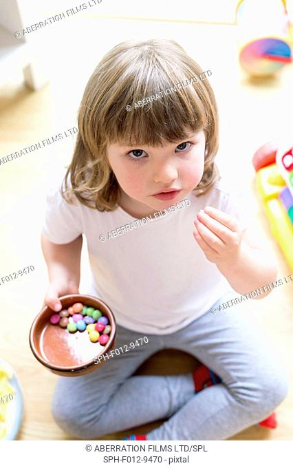 MODEL RELEASED. Young girl sitting on the floor with a bowl of sweets