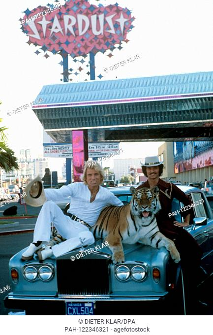 Siegfried (l) and Roy (r) with one of their tigers on the hood of a Rolls-Royce in front of the Stardust Hotel in Las Vegas in August 1978
